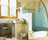 Bathroom with Mediterranean ambiance; masonry washstand against half-height partition wall screening shower with tiled wall and wall painted blue