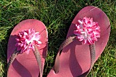 Pink flip-flops with artificial flowers on straps on lawn