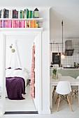 Bücherregal über offener Schlafzimmertür und Blick auf Bett mit violetter Tagesdecke, seitlich offene Küche mit Essplatz