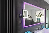 A wall mirror with integrated pink LED lighting on a grey-tiled wall