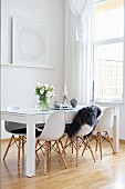 White shell chairs and table with glass top in modern dining room