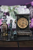 Table clock and ethnic animal figurine next to glass perfume bottle