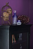 Vintage bird cage on antique, glass-fronted cabinet against aubergine wall