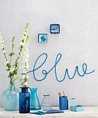 Various blue vases against a wall with the word 'blue' knitted on the wall