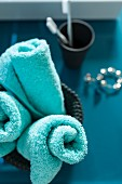 Rolled, turquoise towel in a container