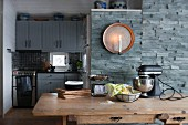 Wooden dining table, candle sconce on stone wall and kitchen integrated into niche