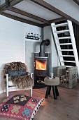 Sessel mit Tierfell, folkloristisches Bodenkissen und Hocker vor Kaminofen mit Feuer in einer Hütte