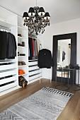 Ankleidezimmer mit offenem Kleiderschrank, schwarzem Kronleuchter und Bodenspiegel