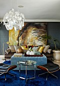 Dramatic painting on dark grey wall in living room with pale blue ottoman and classic designer furnishings