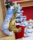 Zwei verzierte Nikolausstiefel als Weihnachtssschmuck an Türgriff hängend