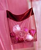Weihnachtliche Baumanhänger in Tasche eines pinkfarbenen Chiffonvorhangs
