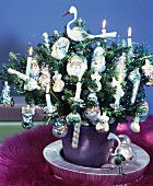 Tiny Christmas tree lavishly decorated with lit candles & baubles