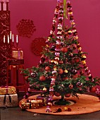 Christmas tree with red decorations and garlands of carnations