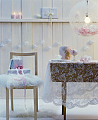 Romantic Christmas arrangement in white with lace tablecloth, furs & baubles