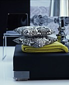 Blanket and black and white, floral scatter cushions on black pouffe in living room
