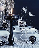Arrangement of crockery, baubles & candlestick on black and white Christmas table