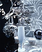 Christmas arrangement of crockery, vase, fairy lights & wrapped gifts in black and white