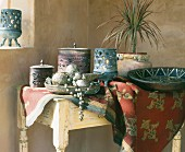 Oriental-style bowls and lidded jars on tablecloth on rustic table in corner