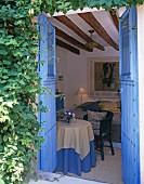 Blick durch offene, blau gestrichene Tür ins Wohnzimmer