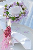 Candle lantern decorated with wreath of purple flowers and bird ornament made from glittering pink beads on place setting