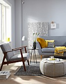 A pouffe in front of a sofa with cushions, a side table and a retro floor lamp against a wallpapered piece of chipboard