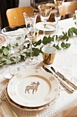 Table festively set with eucalyptus branches and stag motifs on plates