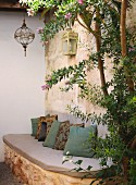 Stone bench with seat cushion & scatter cushions in secluded corner of terrace