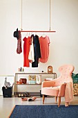 Women's clothing hanging from a floating red clothes rail with an open shelf in a retro room