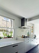 Bright kitchen with raised hob beneath extractor hood