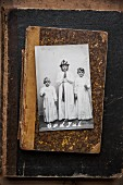 Photo of girls dressed for St Lucy's day celebration on battered, old book