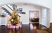 Red and white wrapped gifts under Christmas tree decorated with fairy lights in spacious hallway of American country house