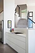 Küchenzeile mit weißem Unterschrank vor Brüstungsmauer, im Hintergrund Treppenaufgang, schwarzes Geländer an Betontreppe