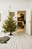 Decorated Christmas tree, animal-skin on white wooden floor and view of balloons and bookcase through open door
