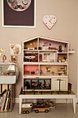 Dolls' house on stool below heart-shaped clock on wall