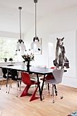 Schwarzer Retro-Esstisch mit zwei roten Stühlen, Industriependelleuchten in skandinavischem Esszimmer