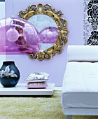 Round, gilt-framed mirror on lilac wall, white chaise and retro pendant lamp