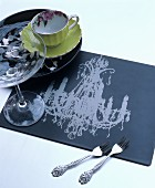 Table mat printed with chandelier motif, china cup and Champagne saucer