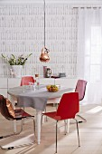 A pendant lamp with a copper shade above a round table with red chairs in a room with cutlery patterned wallpaper