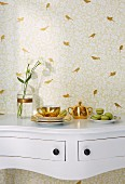 A white console table against a wall with golden bird silhouette wallpaper