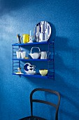 Crockery on a blue shelf on a wall with a blue faux uni patterned wallpaper above a partially visible black chair