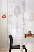 Wallpaper with a large-format, retro cutlery pattern and a semi-solid pattern in a dining room