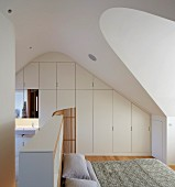 Designer attic bedroom with white fitted wardrobes and ensuite bathroom