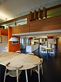 View across dining table into open-plan, designer kitchen below wood-clad gallery with orange partition wall