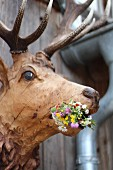 Carved wooden stag's head decorated with wild flowers on wooden wall