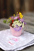 Cup of wild flowers on rustic napkin