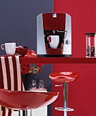 Bright red, glossy bar stool at red kitchen counter with espresso machine and white cups