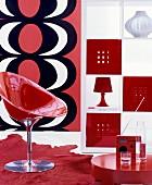 Wohnbereich mit rotem Schalenstuhl, offenem weißem Regal und Wanddekoration mit rot-weiß-schwarzem Muster im Retrostil