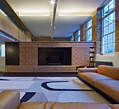 Elegant living room walls in loft apartment; exposed masonry and wood-clad gallery