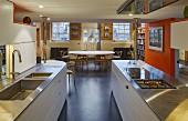 Offene Küche mit orangefarbener Wandscheibe und schwarzem Boden
