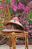 Painted straw hats on bamboo chair outdoors